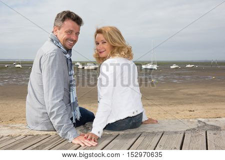 Cheerful Couple Sitting On Wooden Jetty And Looking At Camera