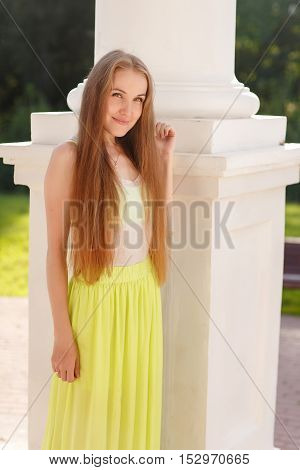Young girl in long yellow skirt standing near column in summer park