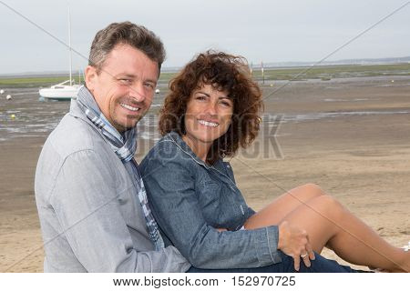 Cute Middle Aged Couple Sitting On The Wooden Jetty