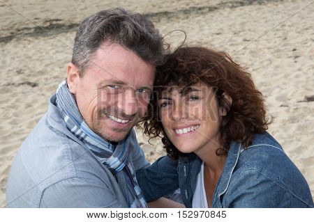 Portrait Of Middle Aged Couple Sitting On The Wooden Jetty