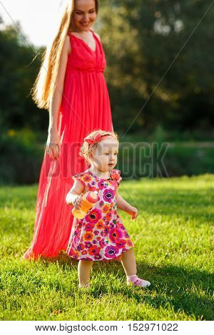 Young mother in long pink dress with small daughter on lawn in park