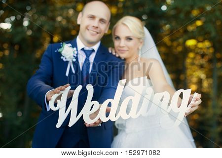 Newlyweds are holding the letters on a walk in the summer park