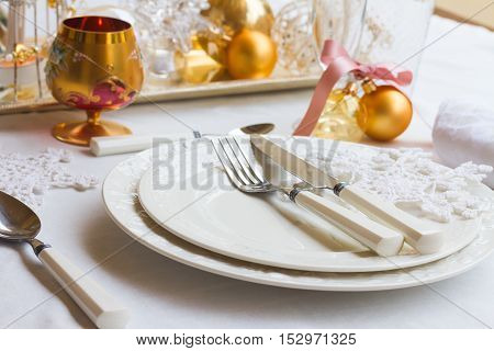 Tableware set for christmas - set of plates, cups and utencils with golden chrismas decorations