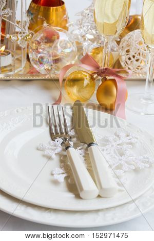 Tableware set for christmas - set of plates, cups and utencils close up with golden chrismas decorations