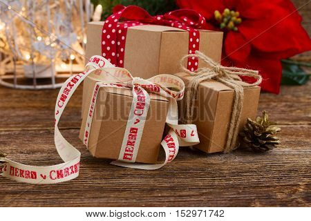 Carton handmade gift boxes on wooden background, poinsetia or christmas star flower in background