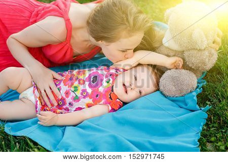 Young woman kissing little girl lying on blue rug beside bear