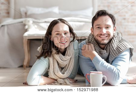 Positive mood. Nice joyful optimistic couple looking in front of them and smiling while being in a great mood
