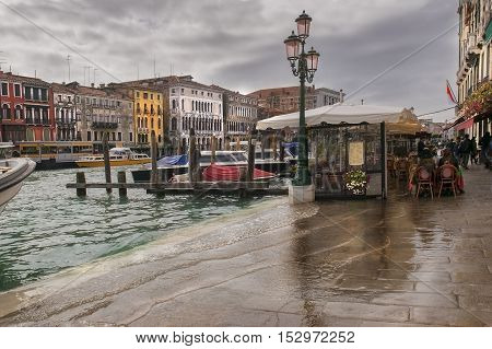 flooded with water promenade of Grand Canal in the rain, Venice, Italy