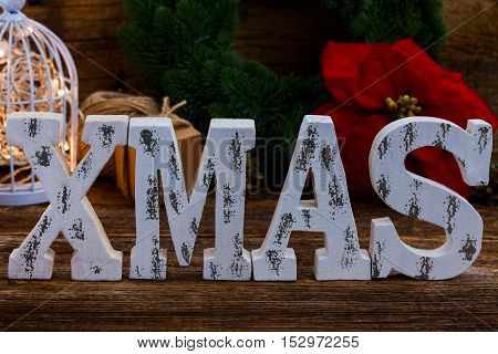 White Xmas letters close up with fir tree wreath in background on wooden table