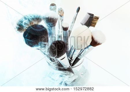 Makeup brushes in a glass vase. Blue smoke.