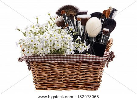 Makeup brushes set in crib with flowers. Chickweed. Isolated. White background.