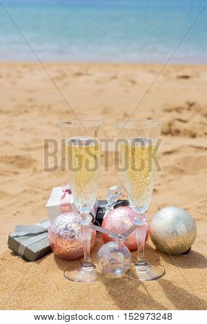 Two glasses of christmas champagne and bubbles with christmas gift boxes and decorations on beach by the sea