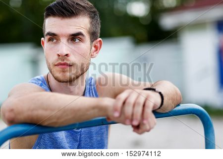 Athlete caucasian young man resting after workout on nature on summer day