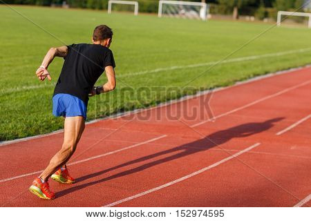 Portrait in full growth of running man on track outdoors on summer sunny day