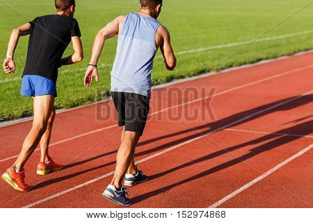 Two strong healthy men jogging on athletics track on a bright sunny day