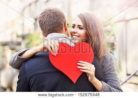 Picture showing happy couple hugging with heart in the city