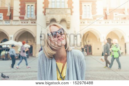 Young female tourist sitting on a chain link fence in an area near the Cloth Hall in Krakow.