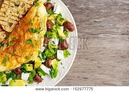 Mushroom, Feta Cheese egg Omelette with Avocado, vegetables, lettuce, herbs and grilled bread