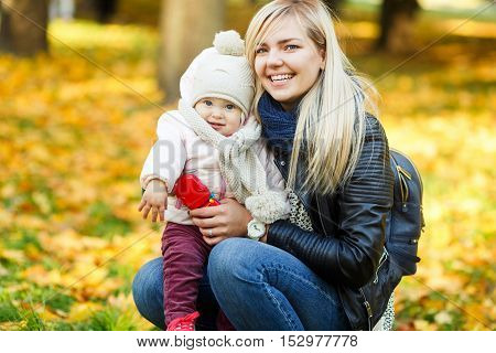 Happy young mother with her little daughter in park among yellow trees