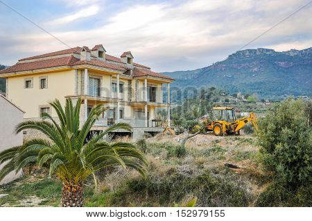 Construction site with unfinished new house and yellow excavator on the background of mountain scene. Horizontal.