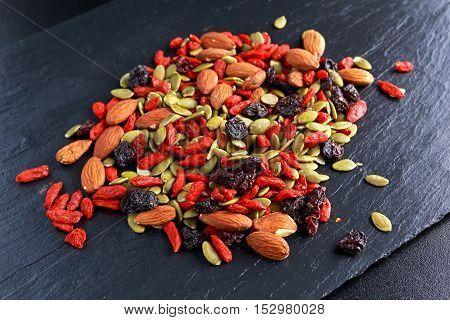 Nut mix snack with raisins, pumpkin seeds, almonds and goji berries on stone board.