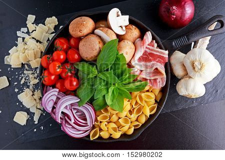 One pot pan pasta with bacon, chestnut mushrooms, cherry tomatoes, red onion, conchiglie and basil leaves.