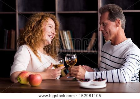 Love. Captivated smiling aged woman and man drinking wine while resting at home and looking at each other and holding hands
