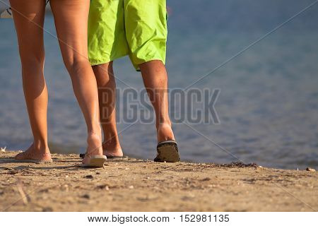 Close up of legs of a couple walking on the beach with flip flop. Summer vacation, vacation concept.