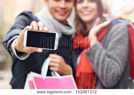 Midsection of young couple shopping in the city with smartphone