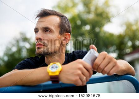 Young man waiting for someone on street with phone in hand