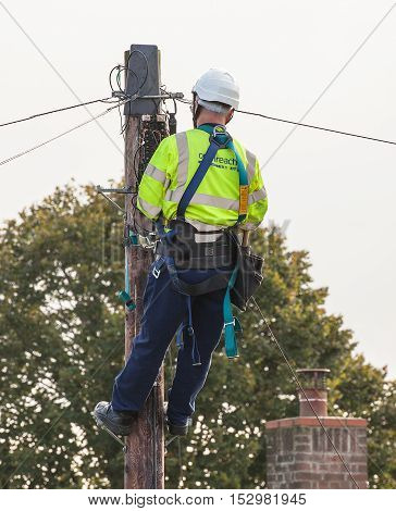 FAKENHAM NORFOLK / UK - 10th OCTOBER 2016: Openreach BT engineer fixing cables up a pole. UK internet and telephone infrastructure provider at work providing internet and telephone services to rural locations