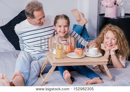 ... breakfast tray on the bed with her grandparents while holding cupcake
