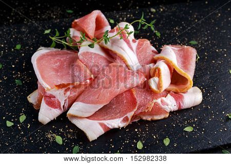 Raw smoked bacon slices on black stone board which herbs.