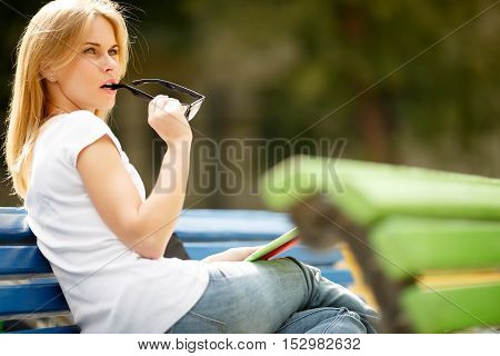 girl turned sitting on bench glasses in hand