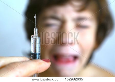 doctor holding a syringe with injection vaccination. Boy is afraid. Teen boy in fear of injection.