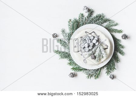 Christmas composition. Blueberry cake with fir branches Christmas dessert. Flat lay top view