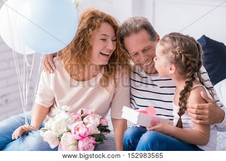I love my caring grandparents. Happy little girl sitting on the bed with her grandparents and receiving presents from them while having fun at home