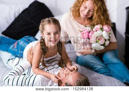 We enjoying our free time. Cheerful little girl playing games with her grandparents while holding cheeks of her grandfather and having fun at home