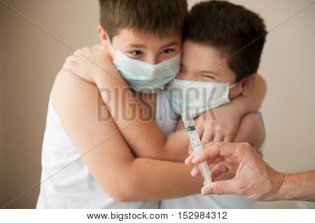 two afraid kids in a surgical mask looking at hand with syringe