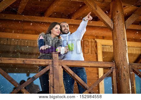 Couple on winter holiday show something in wooden cottage in mountain
