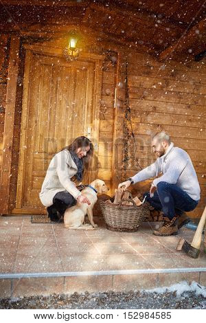 Couple in love with dog in front of weekend cottage