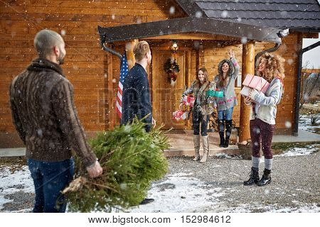 Young group of friends  coming in weekend house to celebrate New Year