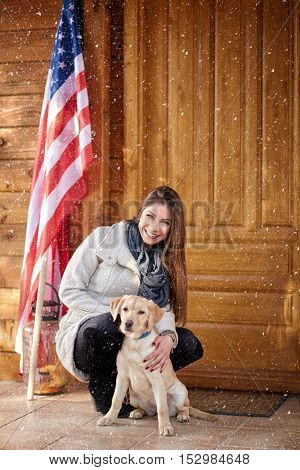 Pretty girl with beautiful dog in front of mountain cottage
