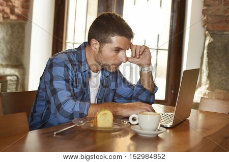 young attractive businessman or student on his 30s wearing casual clothes working or studying with laptop computer at coffee shop having tea cup and cake in modern business self employed concept