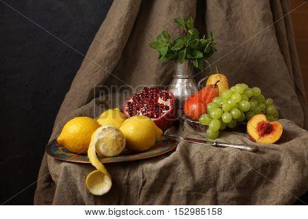 Still life in the Studio, pomegranate, grape, lemon. Beautifully laid on the rough fabric.