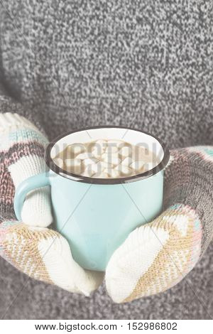 Girl Keeps A Mug Of Hot Cocoa With Marshmallows In Mittens. Toning