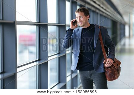 Smartphone business man talking on mobile phone in airport - travel lifestyle. Businessman using smartphone calling on phone walking in corporate building or on work commute in public transit area.