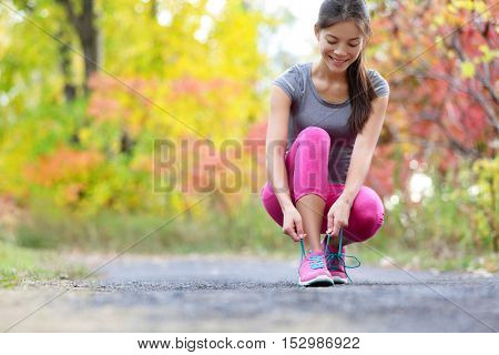 Running shoes woman runner tying shoe lace for run. Happy smiling girl getting ready for jogging lacing run shoe laces. Female sport fitness runner outdoors on forest path in autumn fall season.