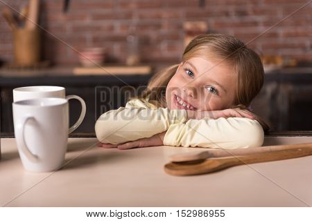 Happiness. Amused smiling little girl sitting at the table while having fun in the kitchen