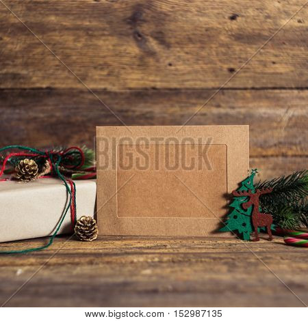 Christmas gift box with cards on a wooden background with candy cane fir branches candle cones.